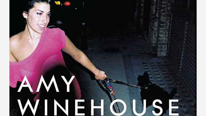 "Amy is dressed in a pink top and is smiling. She is holding a leash with her left hand which has a black dog on the end of it. The text ""Amy Winehouse"" is present in white text while Frank is present in pink text to match her shirt."