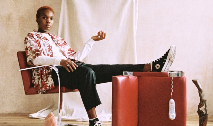 The album cover is a portrait of Arlo Parks, sitting with her foot propped up against the background of a beige curtain