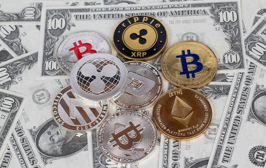 Photo showing cryptocurrency coins sitting on top of 100 dollar United States Bills. Cyptocurrency coins are bitcoins, Ethereum, Ripple, Litecoin, and Dash.