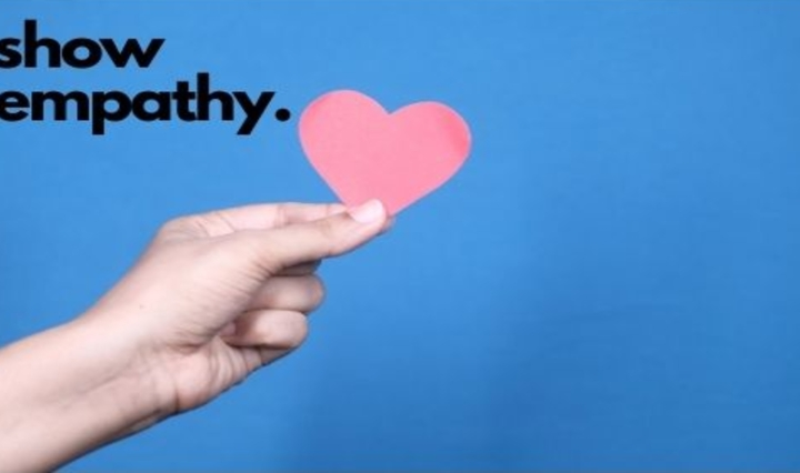 blue background with hand holding a heat with show empathy in black