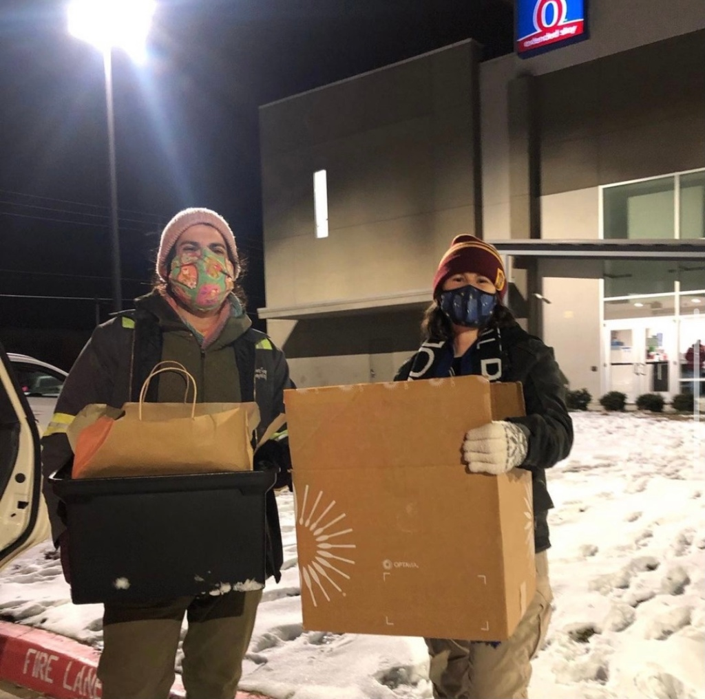 Two HOME Center volunteers pose in front of a motel holding boxes of supplies.