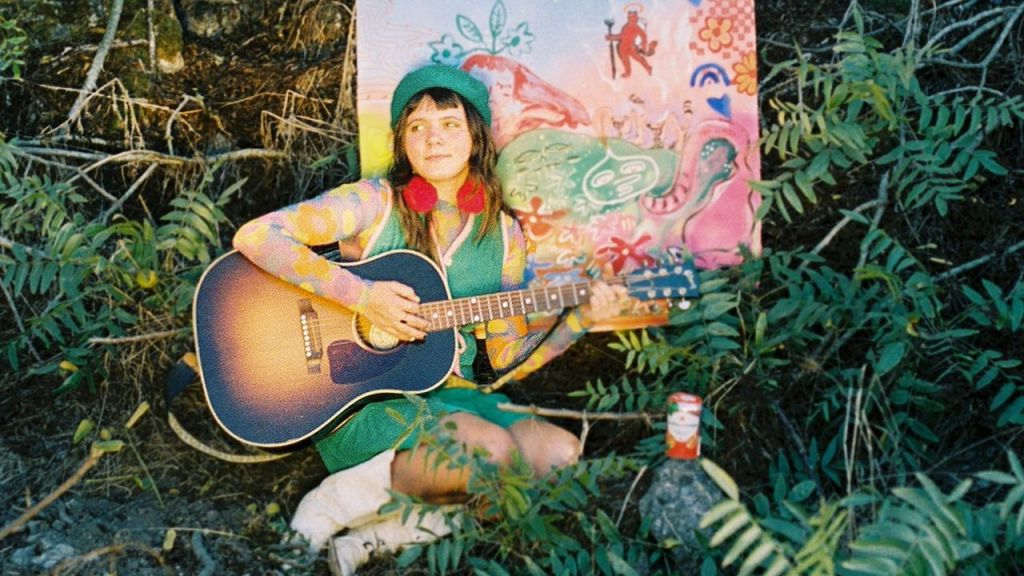 Photo of Mae Powell with acoustic guitar amidst greenery.
