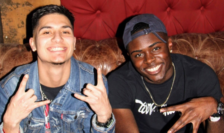 Photo of DJ Ortiz and Doogie C. smiling and sitting backstage before a performance.