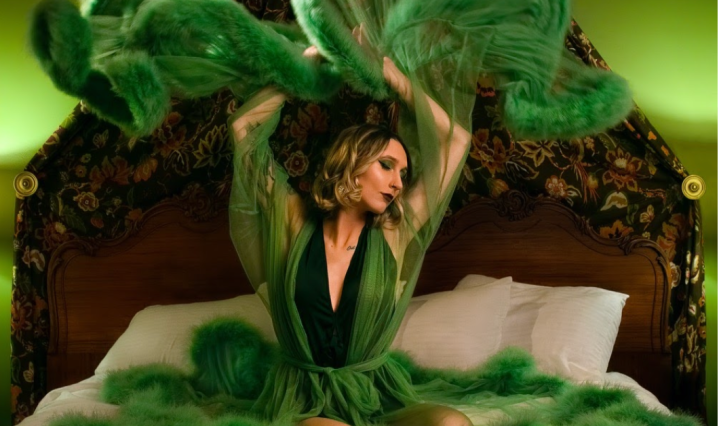 Brooklyn Michelle sitting in the Roosevelt Suite filming for her new music video. She's sitting on a hotel bed in a green dress.
