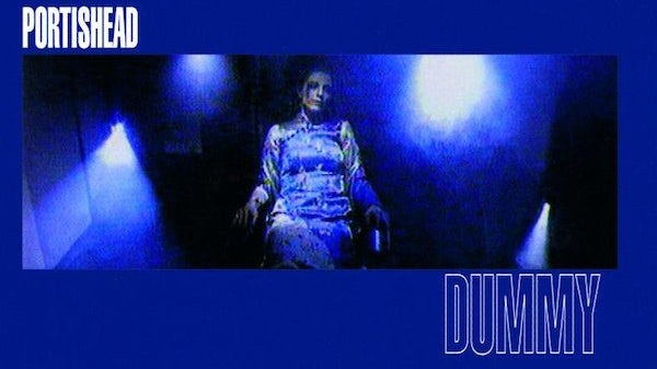 A solid blue background, fronted by a blurry image of a woman sitting under faint lights