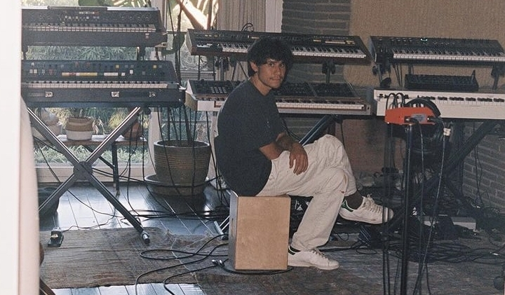 candid photo of frank dukes chilling with synths in the studio