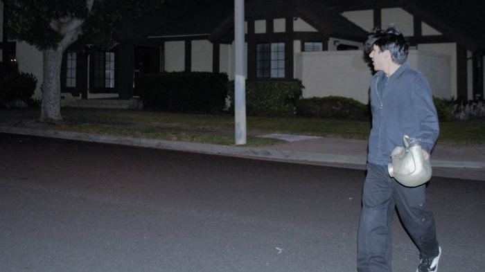 A man walking in a dark neighborhood looking behind him.