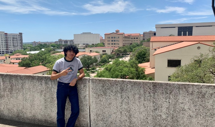 Jesse Rodriguez is posing with peace sign on balcony overlooking the Texas State campus.
