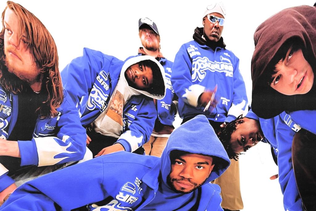 Photo of BROCKHAMPTON members in matching blue jackets.