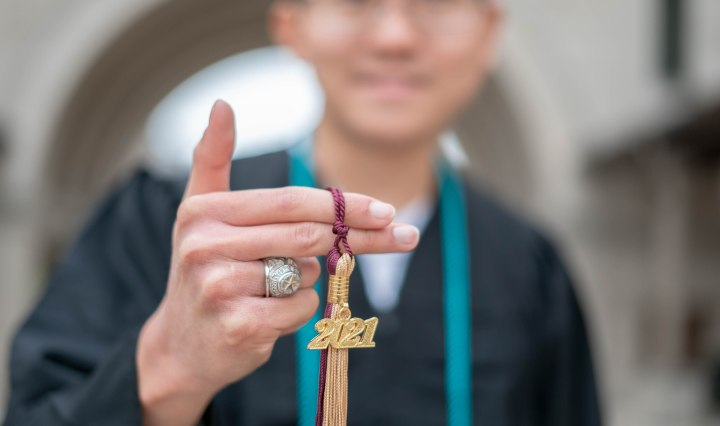 A photo of Tiger Shi posing with his tassel and class ring.