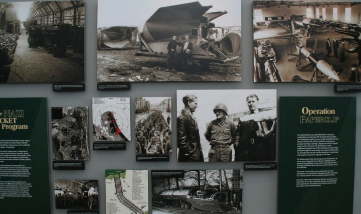 A photo of different photos showing aspects of Operation Paperclip. One photo shows a rocket. Another photo shows two scientists and an army soldier. One photo shows Operation Paperclip with a description of the program. The other photos show railroad tracks, prisoners, vehicles and maps.