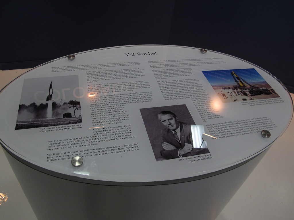 A photo at a museum entitled V-2 Rocket, displaying text that is describing the program with a photo of Wernher von Braun displayed near the bottom middle. To the left and right are pictures of a V-2 rocket.